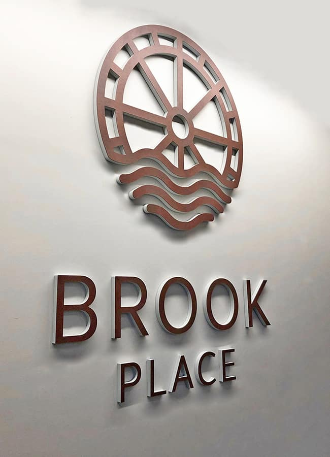 Identity sign designed for the reception for Brook Place Apartments, Sheffield, featuring individual built up letters of the building name and logo faced in a corten steel laminate
