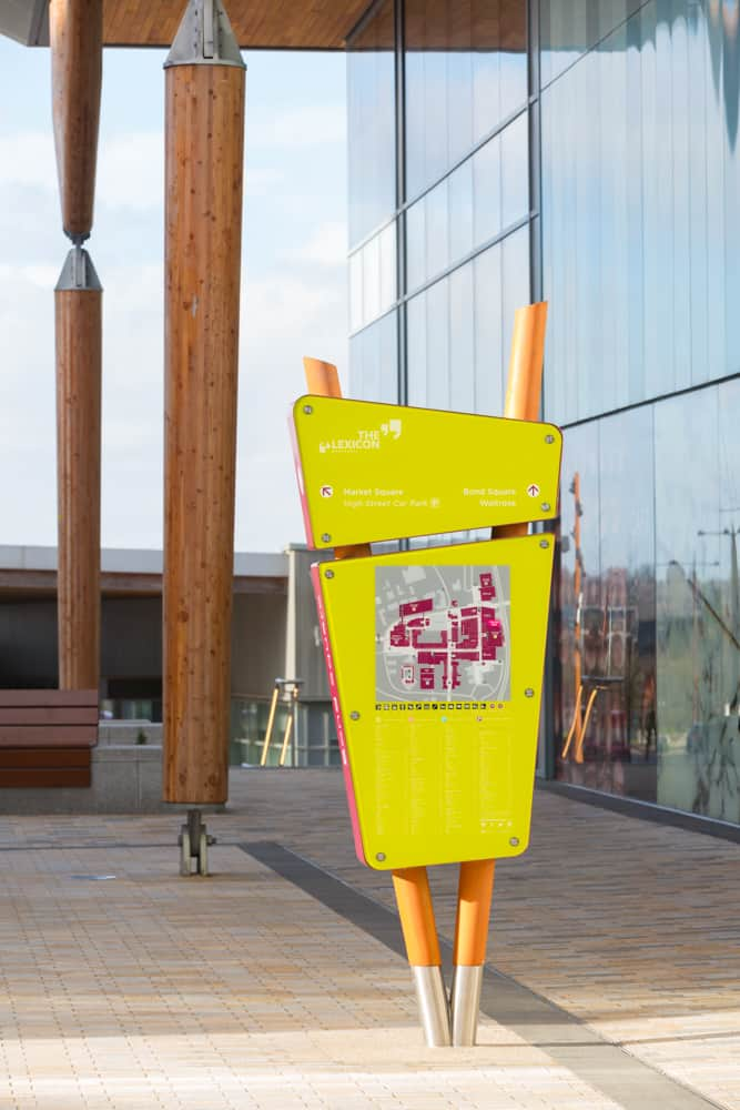 Face on view of the wayfinding totem designed for The Lexicon Bracknell. Consisting of two lozenge shaped sections. The top provides directional information, the larger lower section a town centre map and retailer list