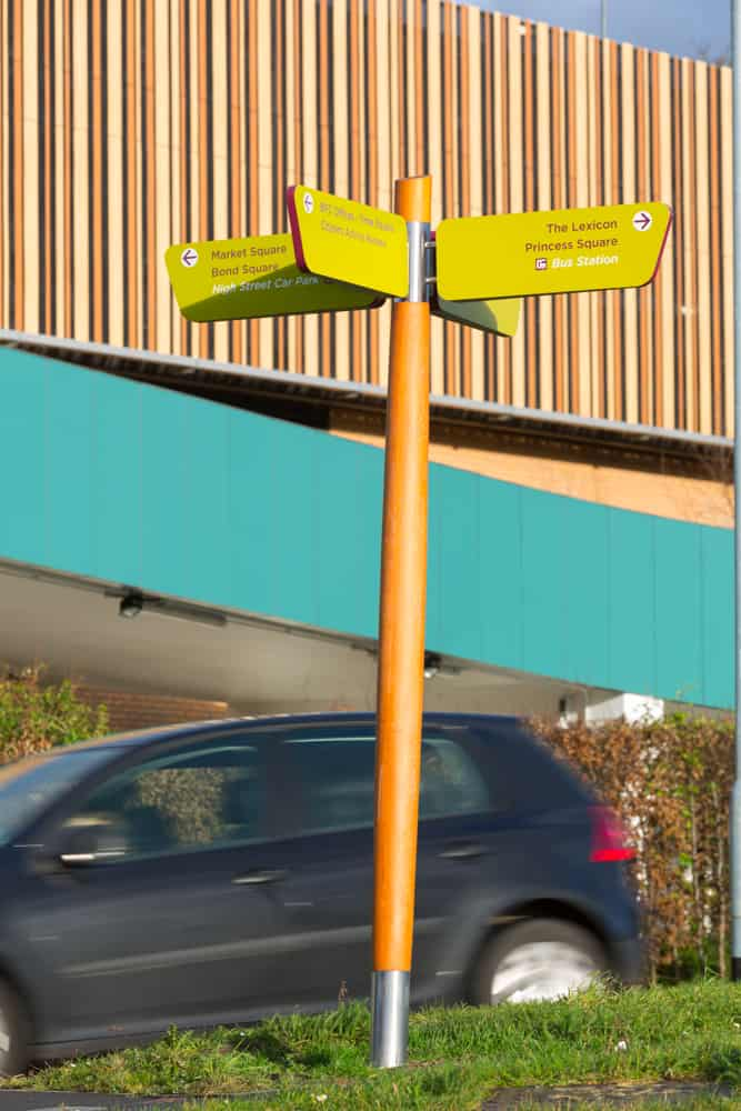 Fingerpost directional prompt signs designed as part of The Lexicon, Bracknell's wayfinding scheme. Using the aubergine and lime brand colours with wooden posts to align with the architecture