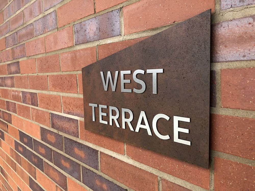 Close up of a sign identifying the West Terrace within Brook Place Apartments. Features stainless steel letters applied onto a mono pitch shaped sign made from a Corten steel laminate