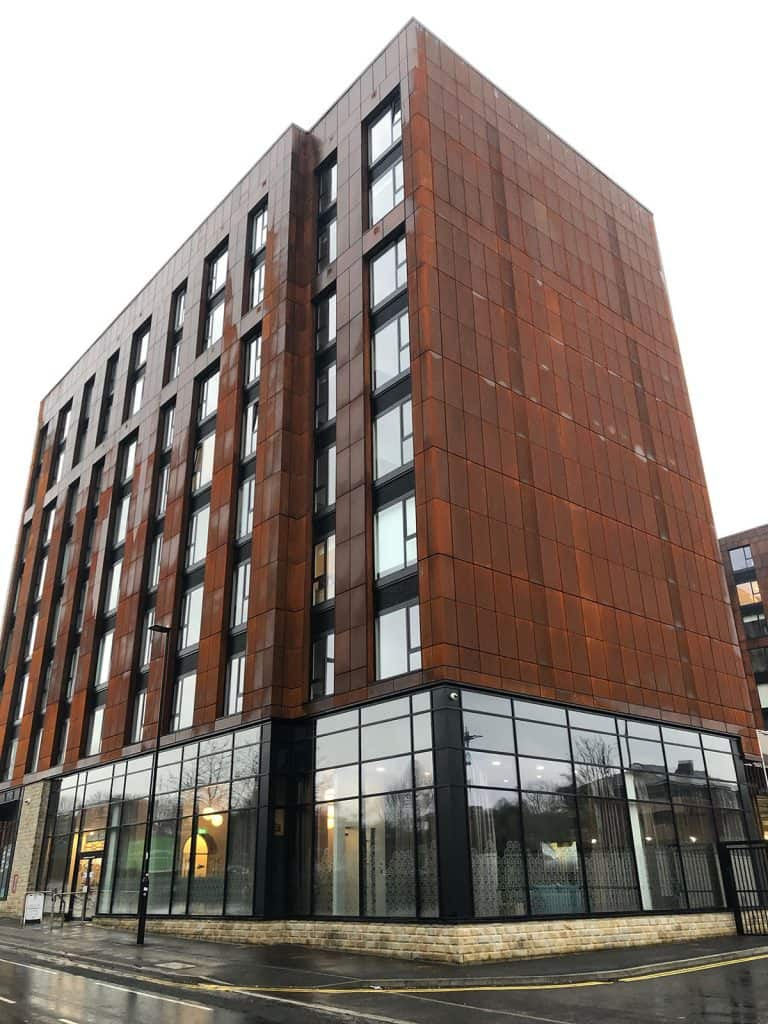 Exterior of Brook Place Apartments, Sheffield with its corten steel facade and glazing to the ground floor.