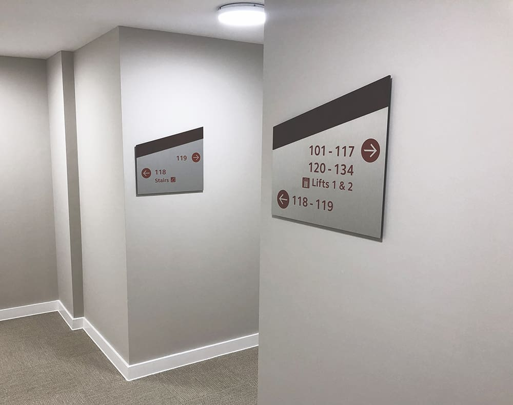 Internal direction signs within Brook Place Apartments, in a mono pitch shape with a dark brown band on the top and corten vinyl coloured letters applied on brushed stainless steel background