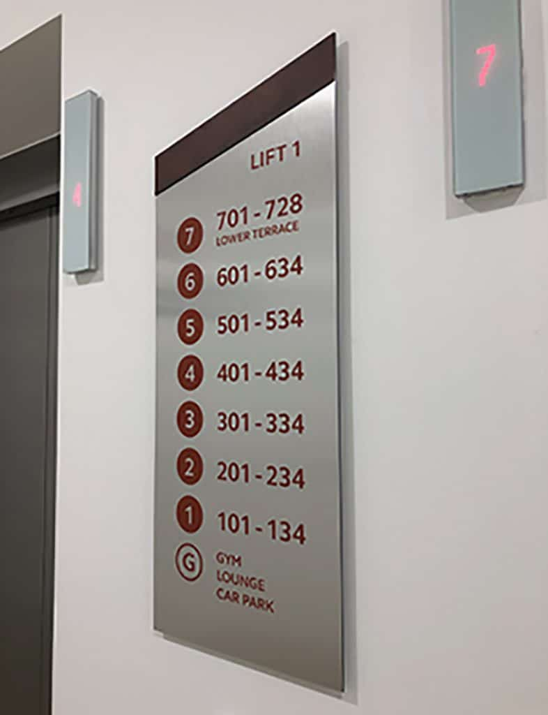 Lift index sign designed for Brook Place Apartments, featuring corten steel vinyl letters on a brushed stainless steel, mono-pitched shape sign