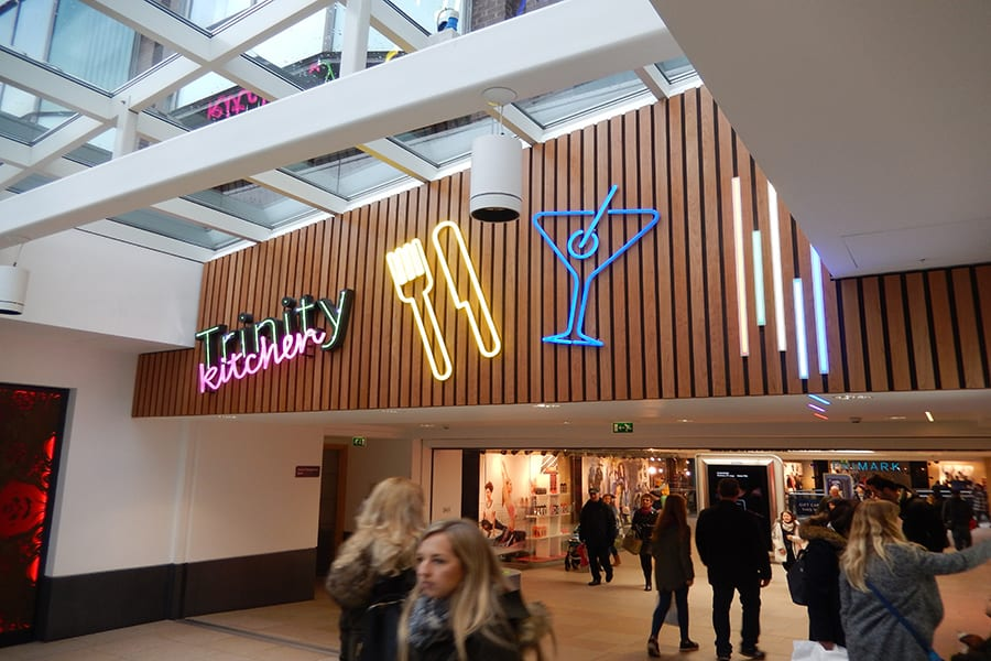 Large neon signs featuring a knife and fork and a cocktail glass together with Trinity Kitchen branding