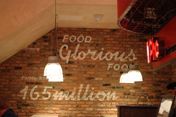 Large white graphics painted on a brick wall. Featuring the slogan 'Food Glorious food' and underneath 'Everyday Britain drinks 165 million cups of Tea