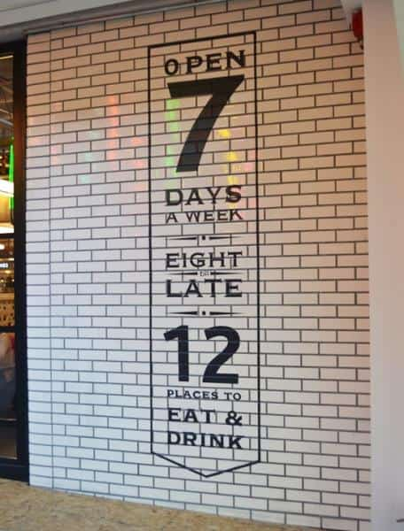 Decorative, floor to ceiling white tiled wall panel. Featuring the words Open 7 days a week, eight till late, 12 places to eat and drink in black lettering..