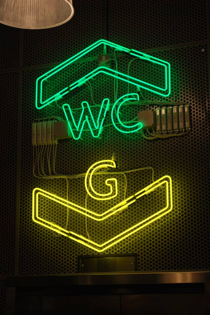 Large neon sign placed over the lift. at the top is the outline of a green arrow head, pointing upwards with the word WC underneath. Below this is yellow is the letter G followed by a downward pointing arrow head