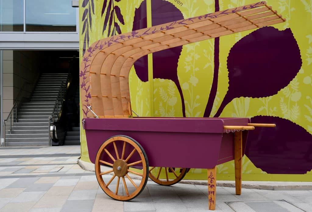 Community barrow, based on a traditional costermonger barrow with wheels and wooden overarching canopy. The base is painted in aubergine and the rest is left in natural wood with a painted leaf motif in aubergine snaking up the leg rests and the canopy edge.