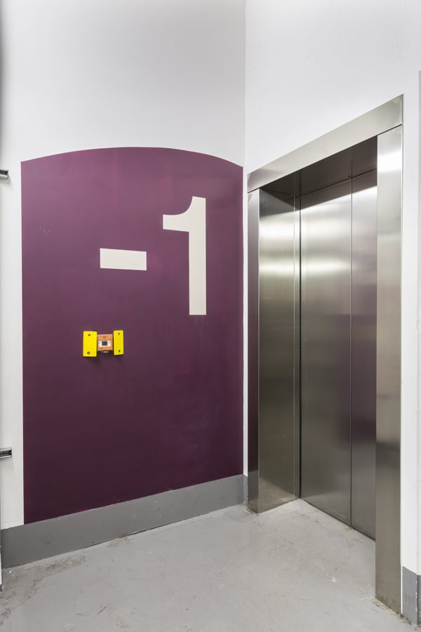 Large level -1 identification sign painted directly onto the wall in the lift lobby in the basement of 20 Fenchurch St