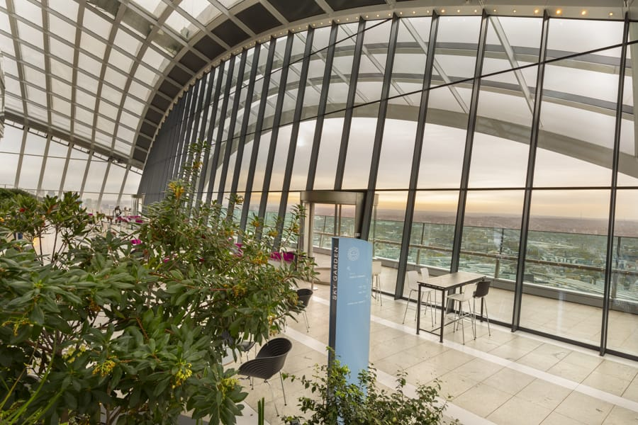 View of a totem sign through the foliage to views of London beyond in the Sky Garden visitor attraction