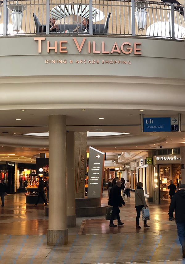 Entrance to The Village Arcade with the high level identification sign and totem at ground level