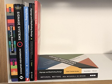 Selection of books on a shelf some are stacked vertically and other are lying flat on the shelf