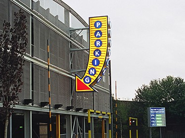 Large arrow sign with a yellow body and red arrow head containing the word parking, pointing to the entrance to a car park