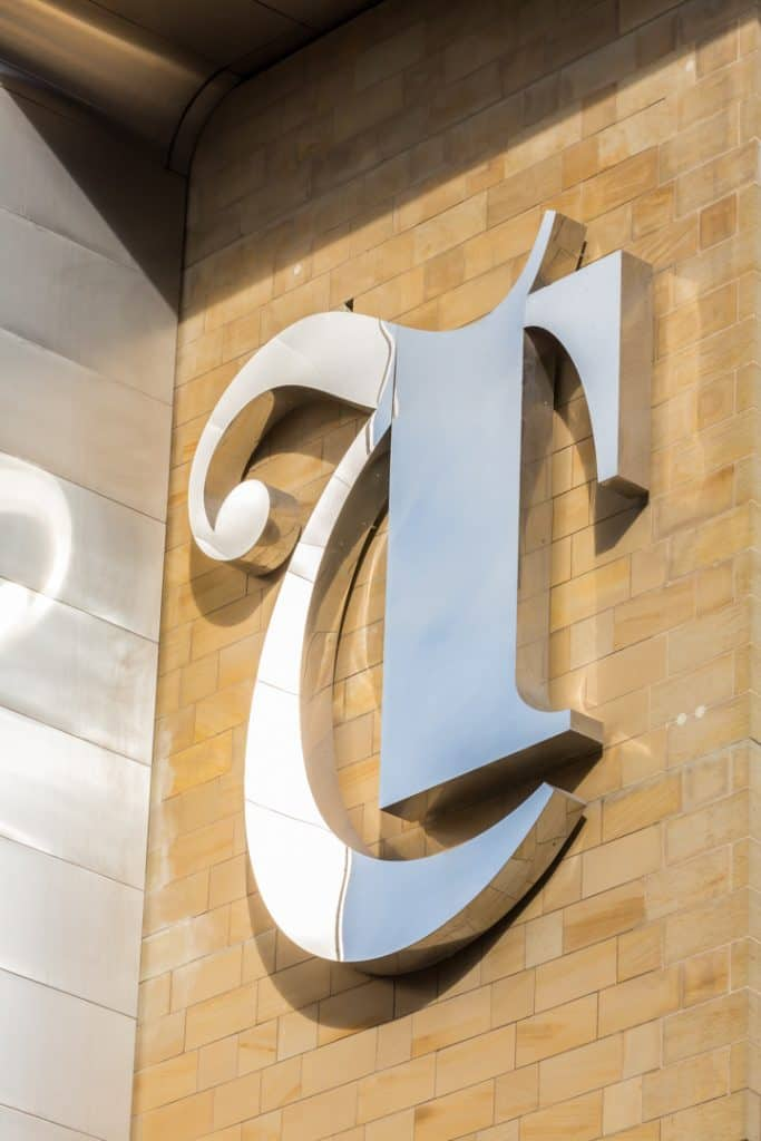 Image of a large letter T in a gothic style made from polished stainless steel applied to a sandstone coloured brick wall.