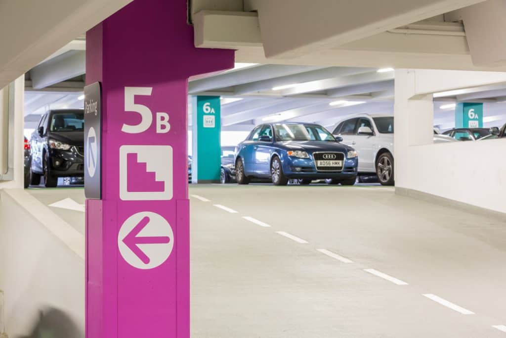 View up a ramp in Trinity Leeds shopper car park showing how colour is used to differentiate between floor levels