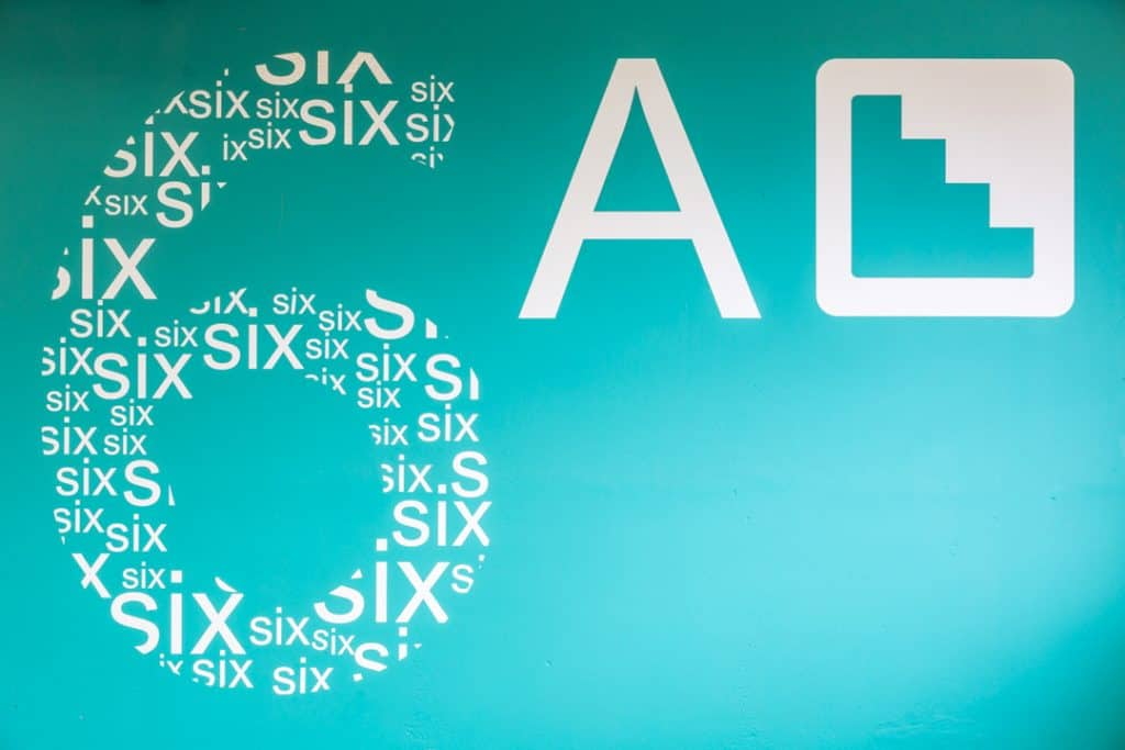 Large scale graphic applied to a wall in a car park showing a block of turquoise colour with a graphic in the shape of a number six, filled with the word six in white lettering of various sizes. Alongside is a capital A and the pictogram used to denote stairs, both in white.