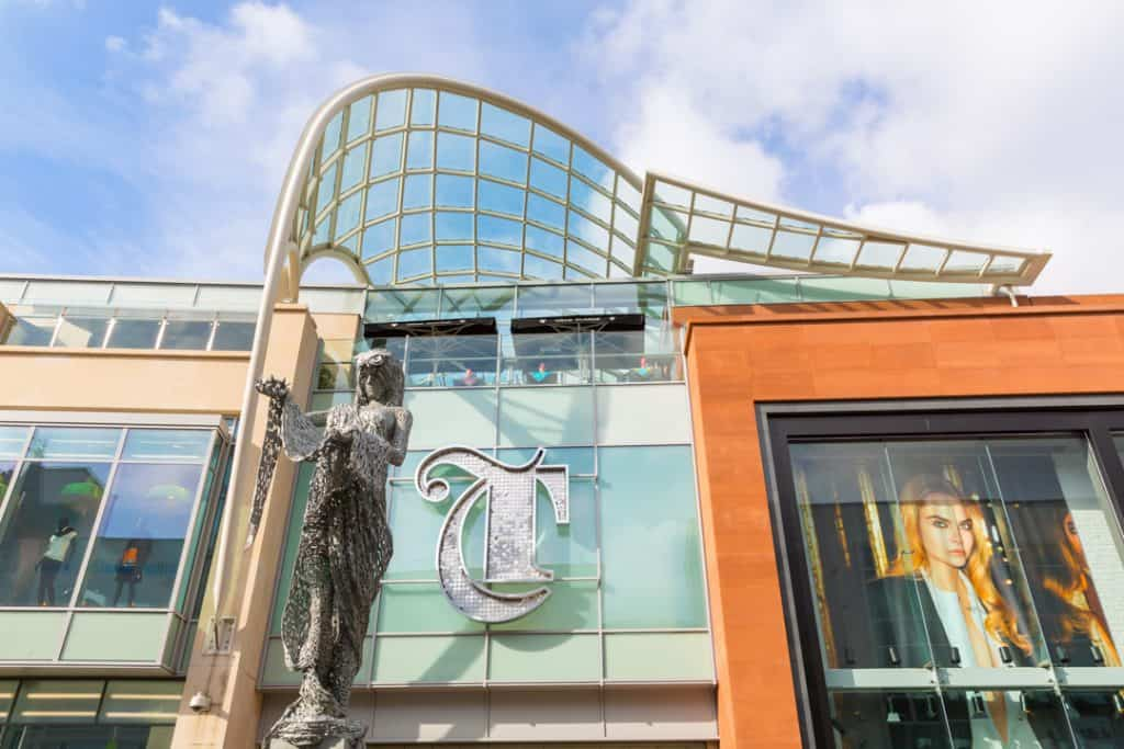 Large letter T in a gothic style, applied above the entrance to The Trinity Leeds shopping centre. The sign is formed from a stainless steel outline and filled with individual metal discs to give it sparkle. In front of the sign is a metal mesh sculpture of the goddess Minerva