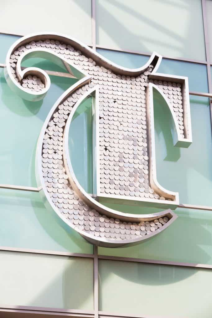 Close up of a the entrance identification sign for Trinity Leeds shopping centre. If feature the outline of a letter T, in a gothic style that is infilled with small metal discs