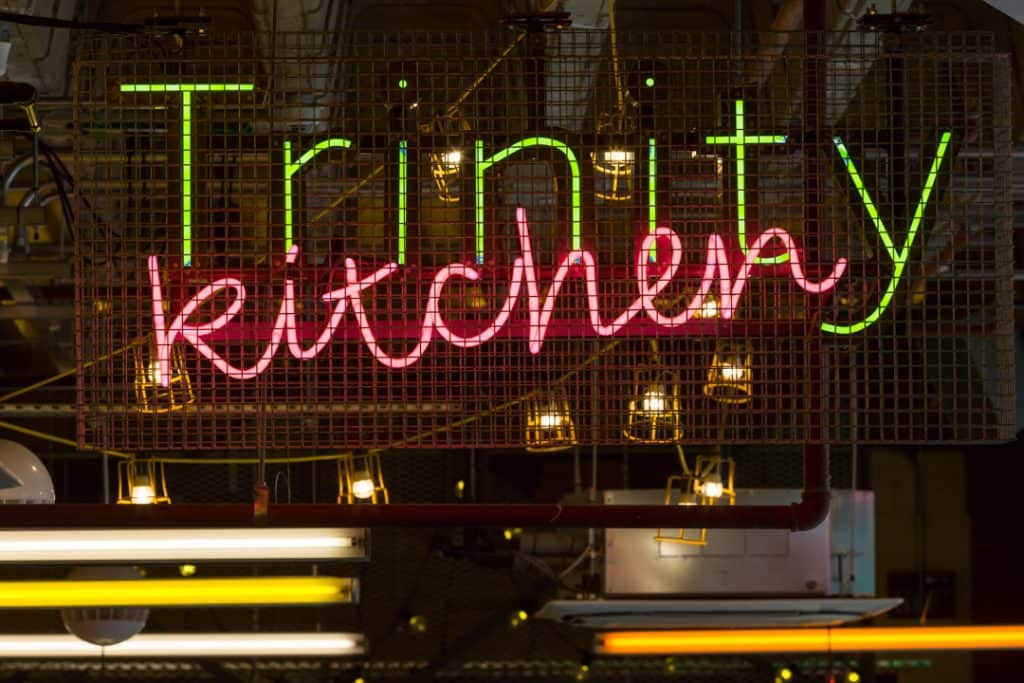 Close up of the Trinity Kitchen identification sign featuring green illuminated individual letters spelling out Trinity, overlaid by the word 'kitchen' in pink neon script. There is a metal chicken-wire sheet in front of the sign and a string of small industrial inspection lights behind. The fixings for the signs and infrastructure for the services is clearly visible.