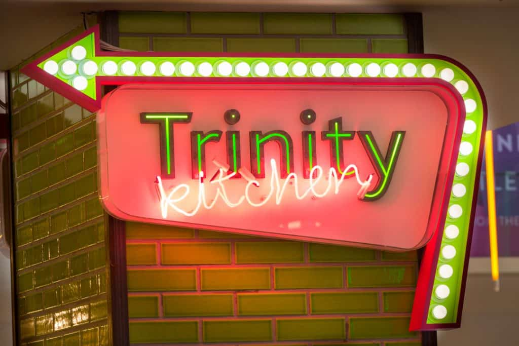 Large illuminated directional sign to Trinity Kitchen, attached to a column finished in green metro tiles. Trinity is written as individual letters, with green illumination with kitchen in a pink neon running across these at angle. The name is contained in a lozenge shape, with an arrow running along the outside from the rights edge across the top. The arrow has white spot lights running along a central recess on a green background. The sides of the arrow shape are pink.