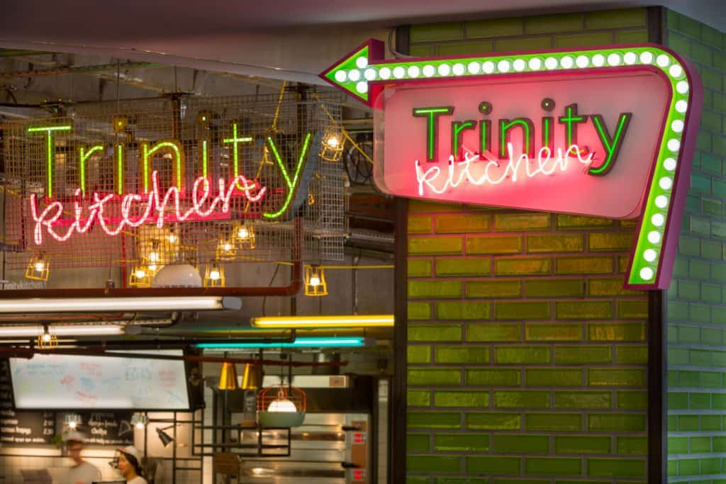Stepped back view showing an identity sign and direction sign for Trinity Kitchen in situ. In both Trinity features as individual letters with green illumination running through the centre. The word kitchen is written in pink neon italics and runs at an angle. The identity sign is suspended from the ceiling and behind a wire mesh screen. The directional sign is attached to a green-tiled column within a lozenge shape. An arrow runs around the right and top edge of the lozenge which is illuminated by white inset spot lights