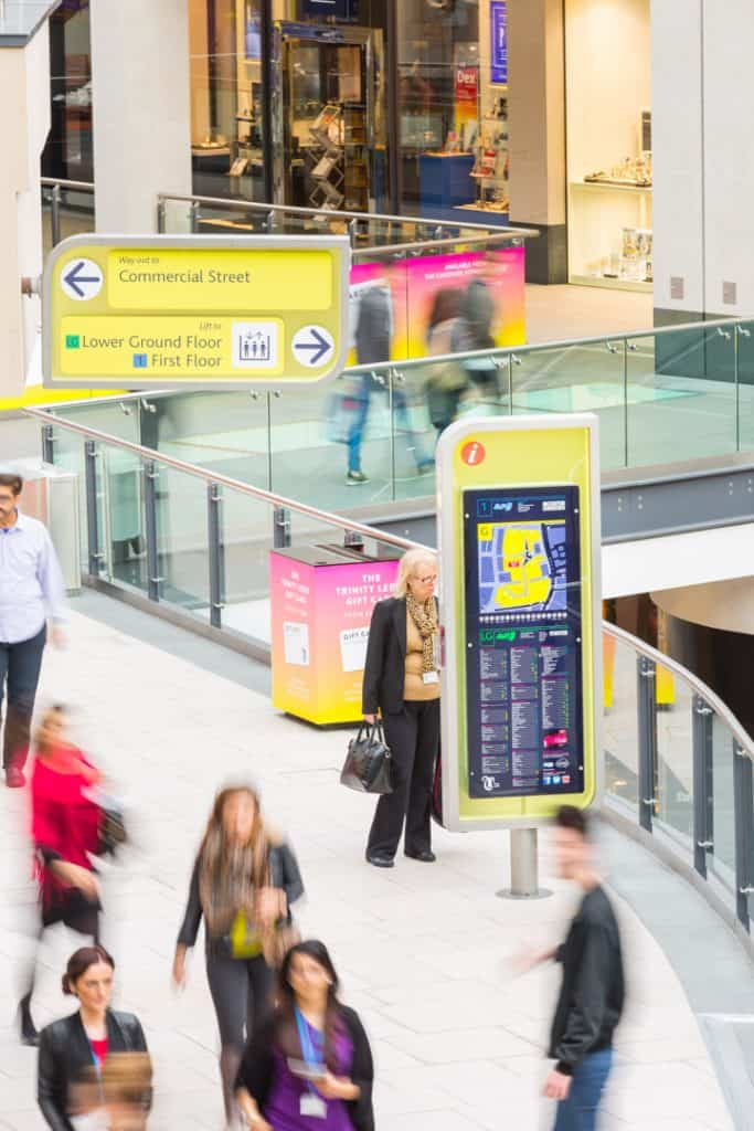 View through ground floor of Trinity Leeds Shopping centre showing the totem and directional sign design
