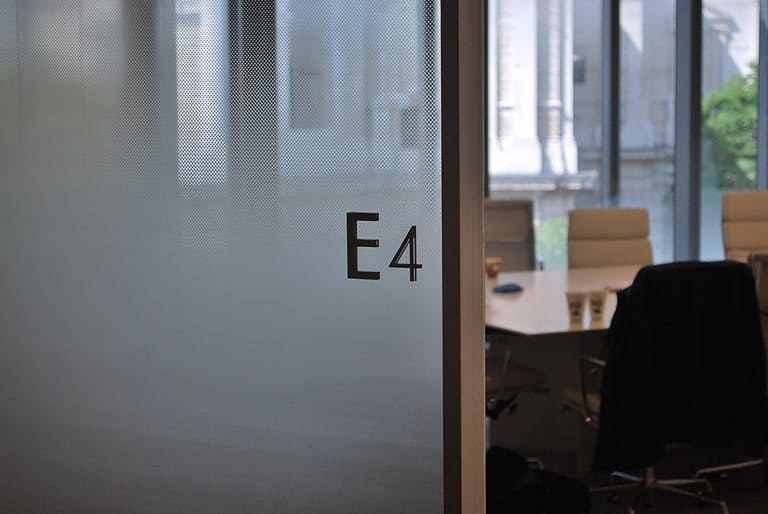 View through the open door to an office. The glazed office wall is covered in manifestation which has a diffused pattern design. The room name E4 is applied to the glass as individual characters