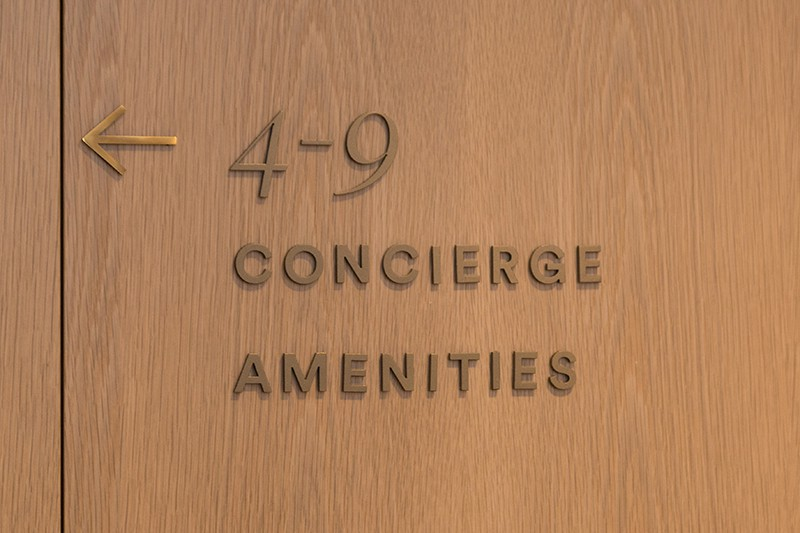 Directional signs on wood panelled wall