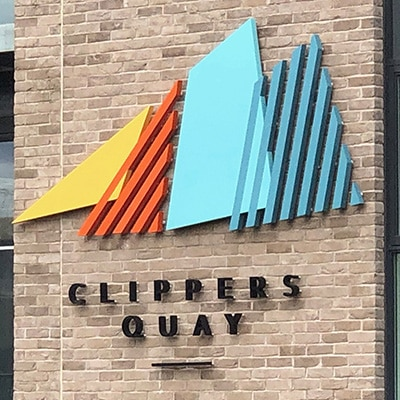 Multicoloured identity sign for Clippers Quay applied to a brick wall. The letters are black and applied as individual 3D characters. The logo type is composed of four overlapping sails – a yellow solid triangle, followed by an orange triangular shaped striated outline, a solid pale blue trapezoid and a further turquoise striated trapezoid.