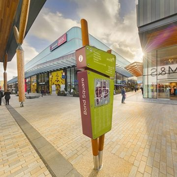 illuminated wayfinding totem signs designed for The Lexicon, Bracknell. The sign is made from two wooden poles that are angled to create a V-shape. These enclose two lozenge shaped signs, in lime green with white letters. The larger bottom sign features a map and list of retailers and amenities. The smaller top one provides directional information to selected locations