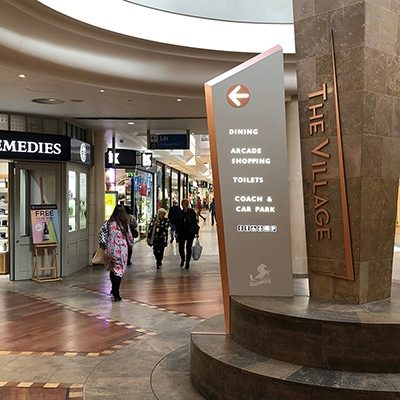 Large totem sign at the entrance to The Village Arcade. The sign is faced in a grey beige colour with a coppery coloured chamfered sides. The content is in white with a copper coloured disc surrounding the directional arrow.