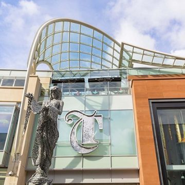 Large letter T in a gothic style, applied above the entrance to The Trinity Leeds shopping centre. The sign is formed from a stainless-steel outline and filled with individual metal discs to give it sparkle. In front of the sign is a metal mesh sculpture of the goddess Minerva.